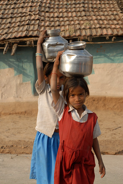 Little girls fetching water from the village water source (well).