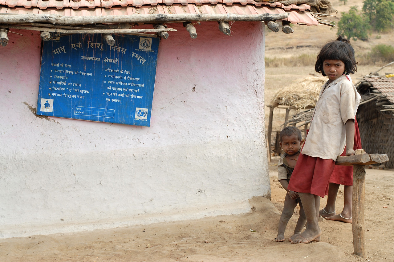 India: Children playing near a centre which is for pre and post natal care. The sign board in Hindi talks about the health care for mother and child. Jan 2007.