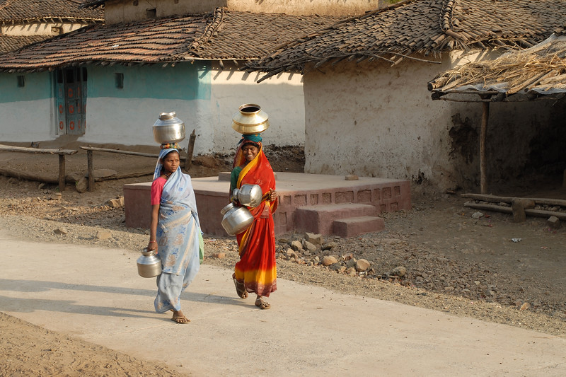 India: Young women carry multiple pots filled with water from the local village hand pump to their homes in a village near Nagpur, Maharashtra. January 30, 2007.
