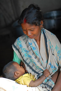 India: A young mother looks on as she breast feeds her child in a village near Nagpur, Maharashtra. Jan 2007.