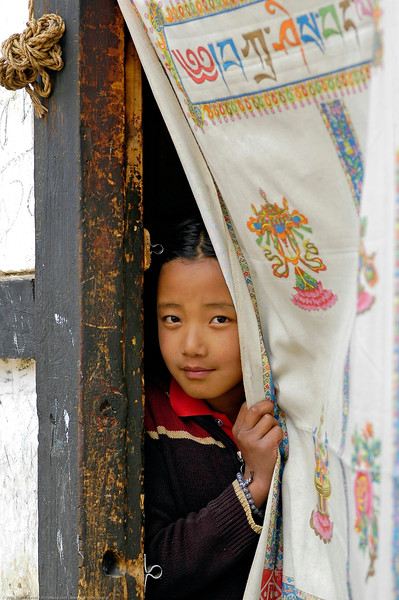 Little girl at the doorway of her home in Paro, Bhutan. The writing on the cloth hung on the door has writing in Dzong (Bhutanese Script)
