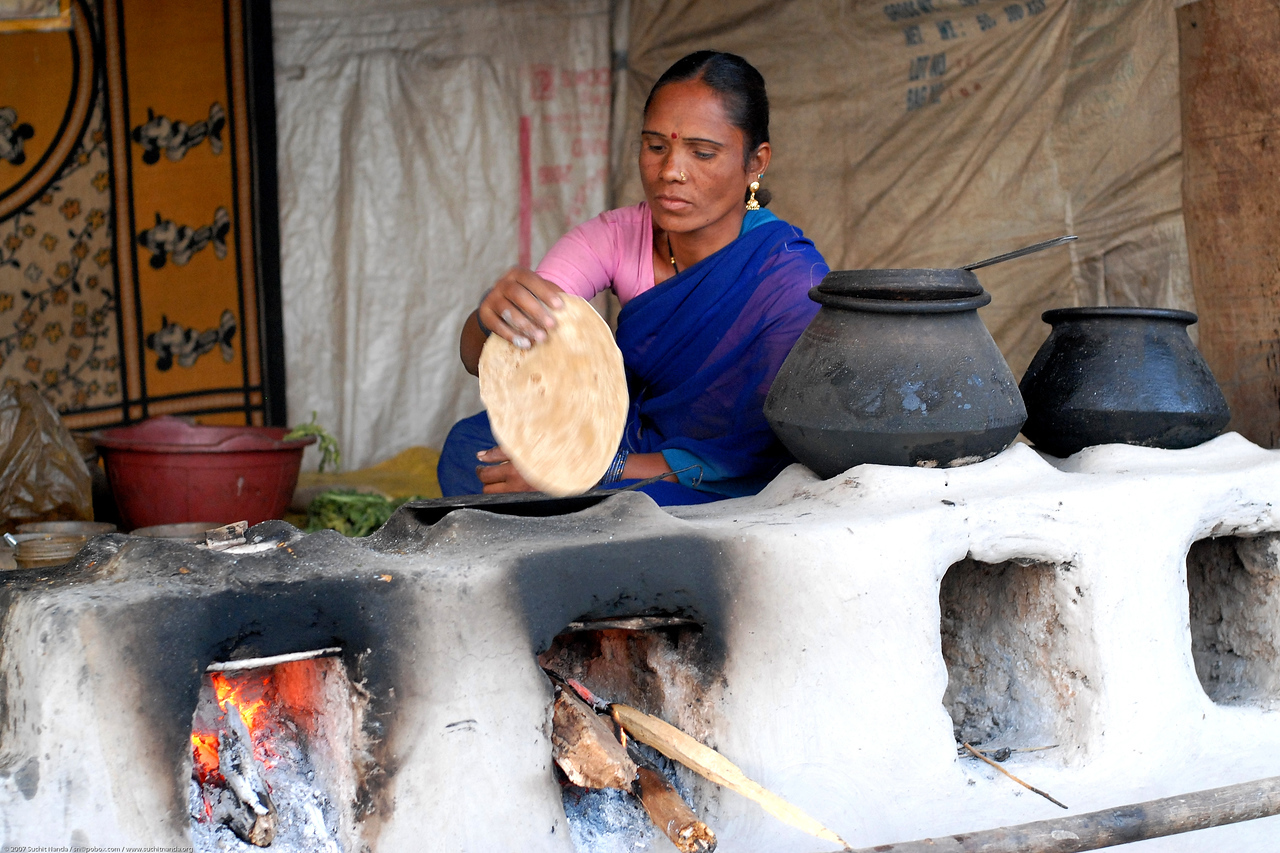 Cooking chappatis (wheat breads) on an open fire. The pots contain dal (lentins) and vegetables. Village near Nagpur, Maharashtra, Central India.