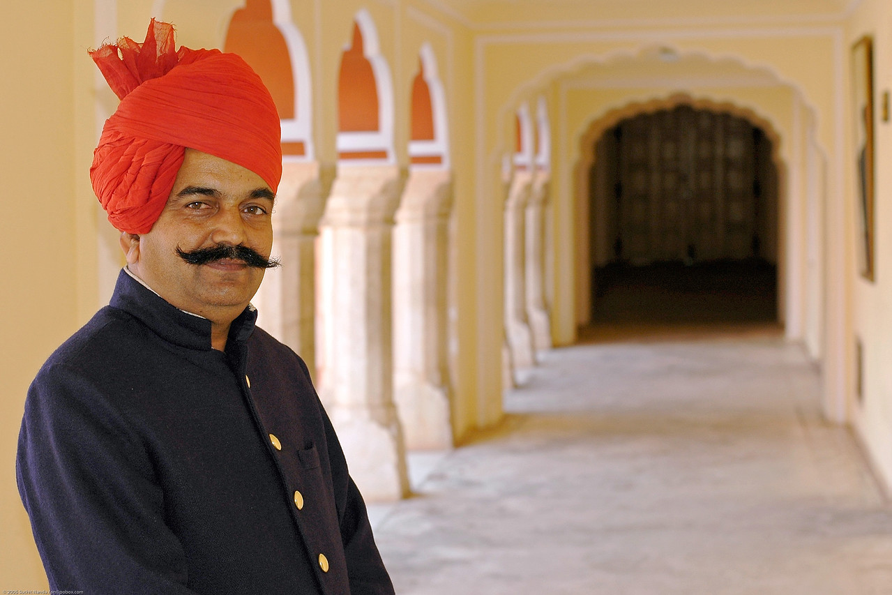 Portrait of an attendant at the Jaipur Palace, in Rajasthan, India.<br /> The Palace with its series of courtyards, gardens and buildings was built by Sawai Jai Singh, but other additions are more recent. The palace is a blend of Rajasthani and Mughal architecture. The son of the last Maharaja and his family still live in part of the palace.