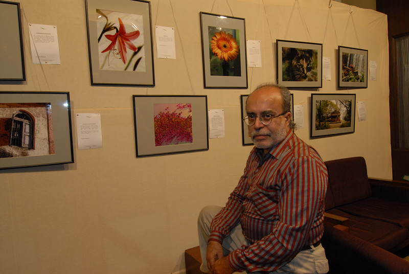 Swapan Mukherjee in front of his pictures exhibited at the Rodas Hotel, Powai, Mumbai