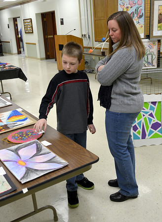 Altamont Grade School fourth grader Tyler Mesnard shows mom Christy some of the work other students did for the annual Children's Art Show sponsored by the Effingham Art Guild. Tyler earned a third-place ribbon in his division.
