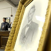 A portrait of Abraham Lincoln looms large as presenter Phil Lewis, left, shares a multitude of facts about the nation's 16th president during a presentation at the Effingham County Cultural Center and Museum Association.