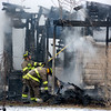 Firefighters deal with the damage after a fire destroyed a home Wednesday at 211 N. Locust Street in St. Elmo. The fire is believed to have been started by an electric space heater.