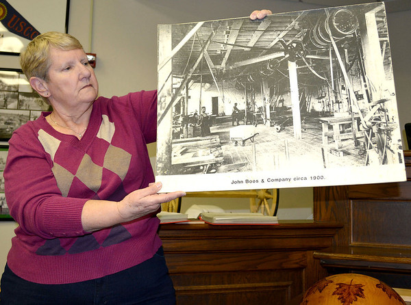 Kathy Boos Fearday shows off a picture of the John Boos & Co. plant from around 1900. She is a direct descendant of company founder Conrad Boos Sr.