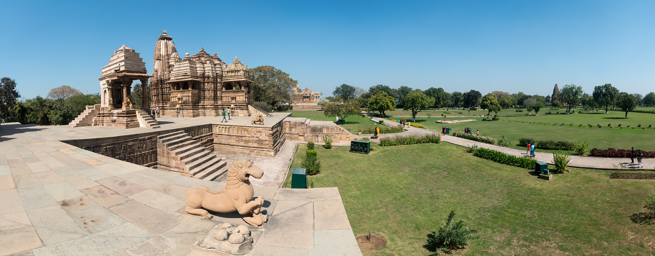 Panoramic view of Devi Jagadambika temple or Jagadambika temple of a group of about 25 temples at Khajuraho, Madhya Pradesh, India. Khajuraho is a World Heritage site. Fine detailed stone carvings at Khajuraho. Khajuraho - Land Of The Moon God is located in the Indian state of Madhya Pradesh (MP) and roughly 620 kilometers (385 miles) southeast of New Delhi. Khajuraho was the cultural capital of the Chandela Rajputs.<br /> <br /> Architecturally they are unique. While each temple has a distinct plan and design, several features are common to all. They are all built on high platforms, several metres off the ground. The stone used throughout is either granite or a combination of light sandstone and granite. Each of these temples has an entrance hall or mandapa, and a sanctum sanctorum or garbha griha. The roofs of these various sections have a distinct form. The porch and hall have pyramidal roofs made of several horizontal layers. The inner sanctum's roof is a conical tower - a colossal pile of stone (often 30m high) made of an arrangement of miniature towers called shikharas.