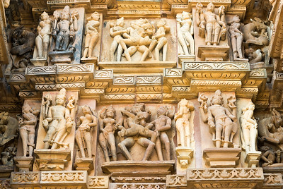 "Stone carved statues at Khajuraho Temple complex. Khajuraho - Land Of The Moon God is located in the Indian state of Madhya Pradesh (MP) and roughly 620 kilometers (385 miles) southeast of New Delhi. Khajuraho was the cultural capital of the Chandela Rajputs, a Hindu dynasty that ruled from the 10th to 12th centuries. The temples of Khajuraho are famous for their so-called ""erotic sculptures"".   Symbolising a medieval legacy, the Khajuraho temples are a perfect fusion of architectural and sculptural excellence, representing one of the finest examples of Indian art. To some, they are the most graphic, erotic and sensuous sculptures the world has ever known. But Khajuraho has not received the attention it deserves for its significant contribution to the religious art of India - there are literally hundreds of exquisite images on the interior and exterior walls of the shrines."