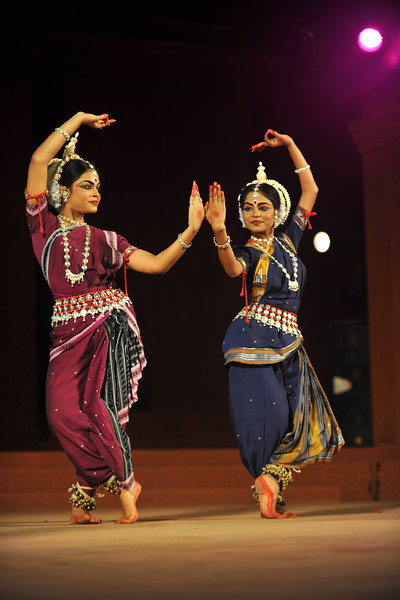 """Odissi dancer Ms. Puspa Panda on the left. Odissi Dance by Meera Das and her Gunjan Dance Academy, Cuttak.<br /> <br /> The Konark Dance & Music Festival held from February, 19th to 23rd, 2010 was organized by Konark Natya Mandap.<br /> <br /> The objectives of the Konark Natya Mandap are to preserve, promote, and project the rich cultural heritage of Orissa and to infuse cultural awareness in the minds of all. Started with painstaking efforts of Guru Gangadhar Pradhan, an internationally renowned Odissi dance teacher. 2010 was the silver jubilee year of the festival. For more details see  <a href=""""http://www.konarknatyamandap.org/"""">http://www.konarknatyamandap.org/</a> <br /> <br /> <br /> The festival takes place in an open-air auditorium and enlivens the spirit of the sculptures of Konark temple which is just a short distance away. The festival brings in the spirit of merry to all the onlookers. The music reverberates and combined with the sounds of the ankle bells of the dancers enthralls the audiences. The elegant steps and expressions of the dancers makes the event so captivating that no one can ever forget it."""