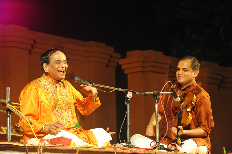 """Padmabibhushan, Dr. M. Balamuralikrishna giving a Carnatic vocal performance. Also seen in the picture is violinist Shri Vittal Ramamurthy.<br /> <br /> The Konark Dance & Music Festival held from February, 19th to 23rd, 2010 was organized by Konark Natya Mandap.<br /> <br /> The objectives of the Konark Natya Mandap are to preserve, promote, and project the rich cultural heritage of Orissa and to infuse cultural awareness in the minds of all. Started with painstaking efforts of Guru Gangadhar Pradhan, an internationally renowned Odissi dance teacher. 2010 was the silver jubilee year of the festival. For more details see  <a href=""""http://www.konarknatyamandap.org/"""">http://www.konarknatyamandap.org/</a> <br /> <br /> <br /> The festival takes place in an open-air auditorium and enlivens the spirit of the sculptures of Konark temple which is just a short distance away. The festival brings in the spirit of merry to all the onlookers. The music reverberates and combined with the sounds of the ankle bells of the dancers enthralls the audiences. The elegant steps and expressions of the dancers makes the event so captivating that no one can ever forget it."""