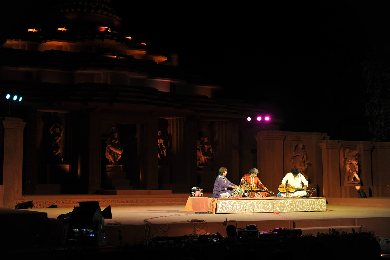 """Mohan Veena duet by Padmashree Pandit Vishwa Mohan Bhatt and Salil V. Bhatt. Pt. Bhatt is the creator of the Mohan Veena instrument from a guitar. The father & son duo had the audience in rapt attention.<br /> <br /> The Konark Dance & Music Festival held from February, 19th to 23rd, 2010 was organized by Konark Natya Mandap.<br /> <br /> The objectives of the Konark Natya Mandap are to preserve, promote, and project the rich cultural heritage of Orissa and to infuse cultural awareness in the minds of all. Started with painstaking efforts of Guru Gangadhar Pradhan, an internationally renowned Odissi dance teacher. 2010 was the silver jubilee year of the festival. For more details see  <a href=""""http://www.konarknatyamandap.org/"""">http://www.konarknatyamandap.org/</a> <br /> <br /> <br /> The festival takes place in an open-air auditorium and enlivens the spirit of the sculptures of Konark temple which is just a short distance away. The festival brings in the spirit of merry to all the onlookers. The music reverberates and combined with the sounds of the ankle bells of the dancers enthralls the audiences. The elegant steps and expressions of the dancers makes the event so captivating that no one can ever forget it."""