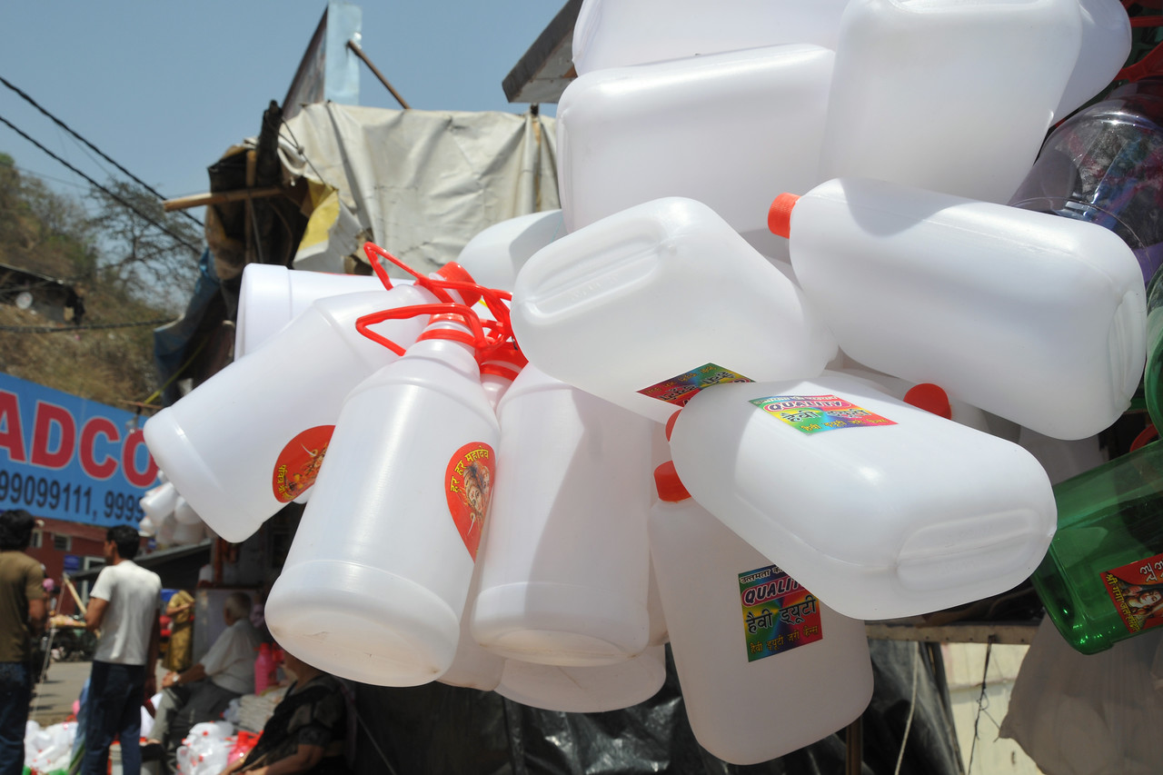 Plastic cans being sold for carrying Ganga-jal (water from river Ganga) back with the pilgrims.<br /> It is believed that Ganga water has medicinal and spiritual powers to cleanse.<br /> Kumbh Mela is the biggest religious gatherings on the planet which takes places on the banks of the river Ganga. The number of pilgrims this year is expected to exceed around five million since the first day Jan 14 till the time it concludes on April 28, 2010. The auspicious days of the shahi snan or royal baths usually draw hundreds of thousands of devotees to the Har Ki Paudi and other banks of the river. Uttarakhand. North India. The occasion draws pilgrims from around the world and severly overloads the infrastructure so most of the city is shut down for any vehicles other than security or emergency services so a sea of humanity walks through the city to get to the bathing ghats.