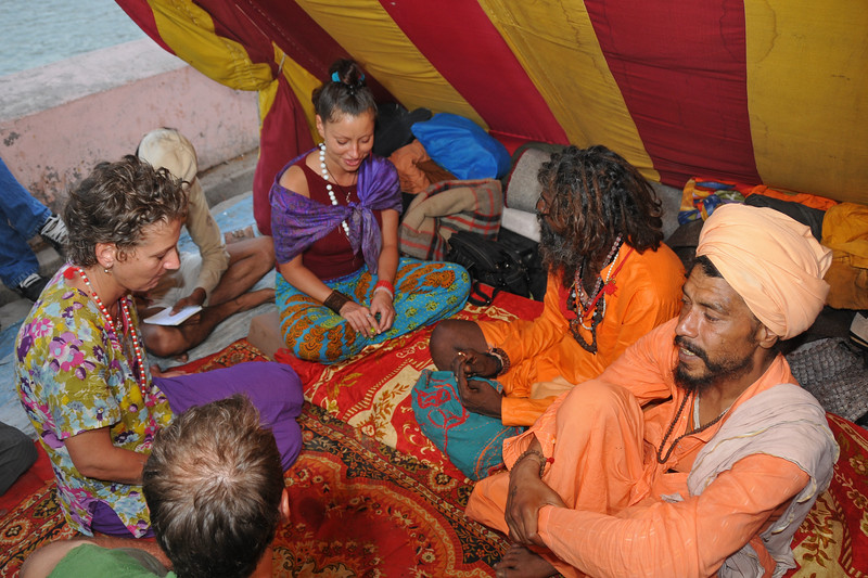 """Many non-Indians come to the Naga sadhus for guidance, dhiksha, or just blessings. Some for mere curiocity and some even to share the hashish. A mixed bag, from which you get what you seek. This man and two ladies were from Romania and when I asked the man if he liked the Kumbh Mela, he said he """"gained lots"""".<br /> <br /> Naga sadhus (naked monks) renounce everything including cloths and rub ash and mud on their bodies. They live only in prayers. Typically with a dhuni (fireplace) in front and chilam (pipe with hashish) they spend time in prayers and meditation. arrives. During Kumbh Mela, the Naga sadhus bless those who come to them.<br /> <br /> <br /> Kumbh Mela is the biggest religious gatherings on the planet which takes places on the banks of the river Ganga. The number of pilgrims this year is expected to exceed around five million since the first day Jan 14 till the time it concludes on April 28, 2010. The auspicious days of the shahi snan or royal baths usually draw hundreds of thousands of devotees to the Har Ki Paudi and other banks of the river. Uttarakhand. North India. The occasion draws pilgrims from around the world and severly overloads the infrastructure so most of the city is shut down for any vehicles other than security or emergency services so a sea of humanity walks through the city to get to the bathing ghats."""