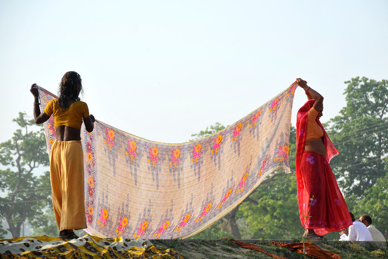 Women drying their cloths after a dip in the holy river Ganga at Haridwar.<br /> <br /> Kumbh Mela is the biggest religious gatherings on the planet which takes places on the banks of the river Ganga. The number of pilgrims this year is expected to exceed around five million since the first day Jan 14 till the time it concludes on April 28, 2010. The auspicious days of the shahi snan or royal baths usually draw hundreds of thousands of devotees to the Har Ki Paudi and other banks of the river. Uttarakhand. North India. The occasion draws pilgrims from around the world and severly overloads the infrastructure so most of the city is shut down for any vehicles other than security or emergency services so a sea of humanity walks through the city to get to the bathing ghats.