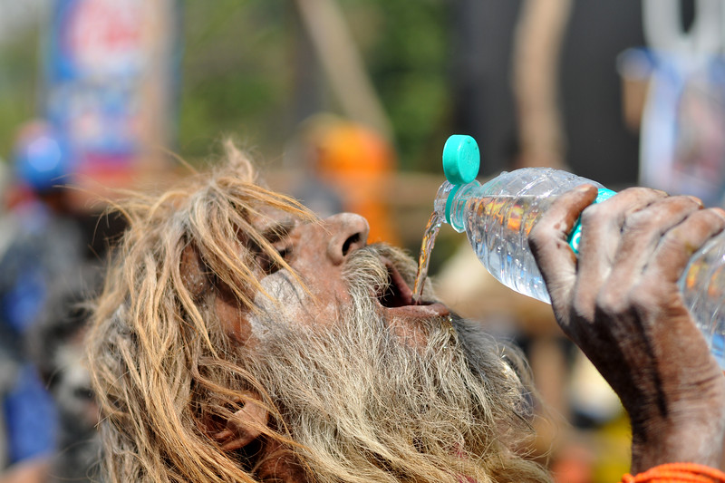 One of the Naga sadhus (naked to sky holy monks) asked for our mineral water bottle to quench his thirst. People around took it as a blessing to offer water to the Sadhus. The sadhus walk barefoot in the heat with great fan fare & beating of drums in a procession to the ghats. As per tradition, the Naga sadhu's have the first right of bathing in the holy Ganga on the occasion of Kumbh Mela's Shahi Snan (royal bath).<br /> <br /> <br /> Kumbh Mela is the biggest religious gatherings on the planet which takes places on the banks of the river Ganga. The number of pilgrims this year is expected to exceed around five million since the first day Jan 14 till the time it concludes on April 28, 2010. The auspicious days of the shahi snan or royal baths usually draw hundreds of thousands of devotees to the Har Ki Paudi and other banks of the river. Uttarakhand. North India. The occasion draws pilgrims from around the world and severly overloads the infrastructure so most of the city is shut down for any vehicles other than security or emergency services so a sea of humanity walks through the city to get to the bathing ghats.
