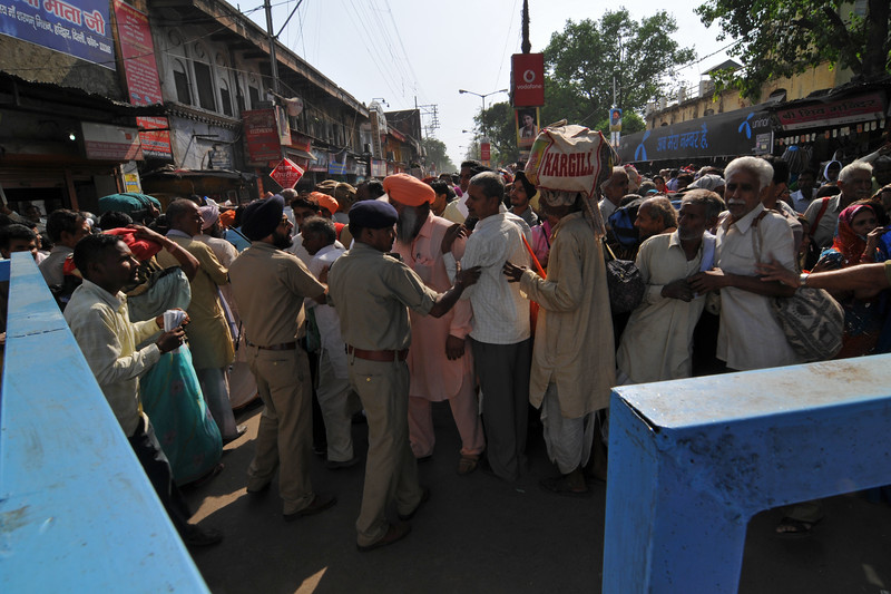 Police having a challenging task of controlling the mobs of people pouring into the city. Barricades were put up and snaking queues were setup leading to the ghats of river Ganga, in Haridwar.<br /> <br /> Kumbh Mela is the biggest religious gatherings on the planet which takes places on the banks of the river Ganga. The number of pilgrims this year is expected to exceed around five million since the first day Jan 14 till the time it concludes on April 28, 2010. The auspicious days of the shahi snan or royal baths usually draw hundreds of thousands of devotees to the Har Ki Paudi and other banks of the river. Uttarakhand. North India. The occasion draws pilgrims from around the world and severly overloads the infrastructure so most of the city is shut down for any vehicles other than security or emergency services so a sea of humanity walks through the city to get to the bathing ghats.