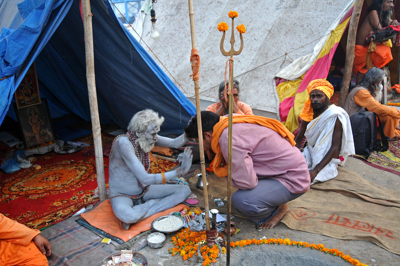 Seeking blessings.<br /> Naga sadhus (naked monks) renounce everything including cloths and rub ash and mud on their bodies. They live only in prayers. Typically with a dhuni (fireplace) in front and chilam (pipe with hashish) they spend time in prayers and meditation. arrives. During Kumbh Mela, the Naga sadhus bless those who come to them.<br /> <br /> <br /> Kumbh Mela is the biggest religious gatherings on the planet which takes places on the banks of the river Ganga. The number of pilgrims this year is expected to exceed around five million since the first day Jan 14 till the time it concludes on April 28, 2010. The auspicious days of the shahi snan or royal baths usually draw hundreds of thousands of devotees to the Har Ki Paudi and other banks of the river. Uttarakhand. North India. The occasion draws pilgrims from around the world and severly overloads the infrastructure so most of the city is shut down for any vehicles other than security or emergency services so a sea of humanity walks through the city to get to the bathing ghats.
