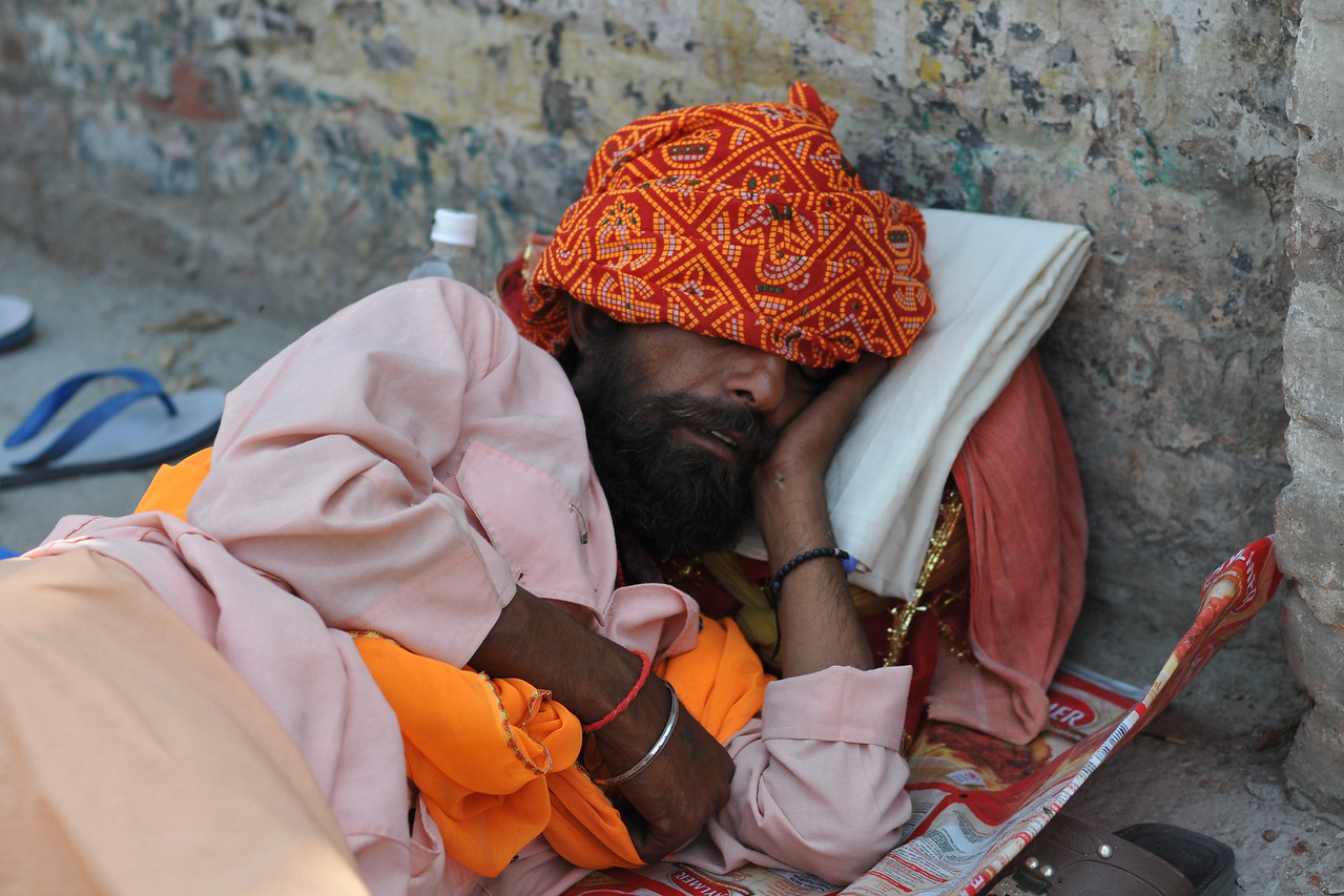 """Taking a quick nap on the streets - literally any small area of land where there is no foot fall.<br /> <br /> Various holy men come to Haridware for the Kumbh Mela and display their various """"skills"""" and """"powers"""".<br /> <br /> Kumbh Mela is the biggest religious gatherings on the planet which takes places on the banks of the river Ganga. The number of pilgrims this year is expected to exceed around five million since the first day Jan 14 till the time it concludes on April 28, 2010. The auspicious days of the shahi snan or royal baths usually draw hundreds of thousands of devotees to the Har Ki Paudi and other banks of the river. Uttarakhand. North India. The occasion draws pilgrims from around the world and severly overloads the infrastructure so most of the city is shut down for any vehicles other than security or emergency services so a sea of humanity walks through the city to get to the bathing ghats."""