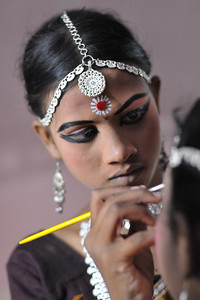 Elder girls help the younger dancers in getting ready by applying make-up.  The Konark Dance & Music Festival 2011 held from February, 19th to 23rd, organized by Konark Natya Mandap. The festival takes place in an open-air auditorium and enlivens the spirit of the sculptures of Konark temple which is just a short distance away.  The objectives of the Konark Natya Mandap are to preserve, promote, and project the rich cultural heritage of Orissa and to infuse cultural awareness in the minds of all. Started with painstaking efforts of internationally renowned Odissi dance teacher Guru Gangadhar Pradhan who unfortunately passed away last year. For more details on the festival see  http://www.konarknatyamandap.org/ and http://konarkfestival.com/
