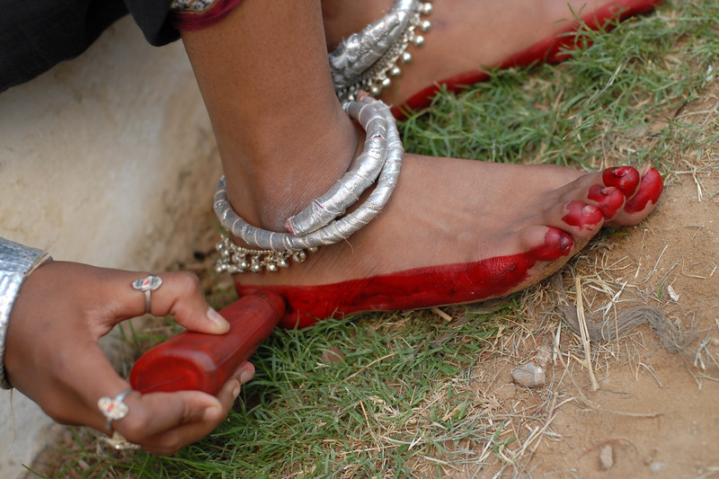 Ladies applying colour on their feet as part of getting ready. The troupe from Orissa performanced a song and dance routine at the Rajasthan Day Celebrations in Jaipur, March/April 2007, India.<br /> <br /> With the aim of showcasing Rajasthan State's culture & heritage and reviving the traditional sports, cuisines and folk-art, Rajasthan Diwas Celebrations were held from 21st March to 30th March 2007. Craft-Bazaar, Food Festival, Night Bazaar, Sports competitions, spectacular fire-works, Mega Cultural Concerts, and competitions for school students were organized.