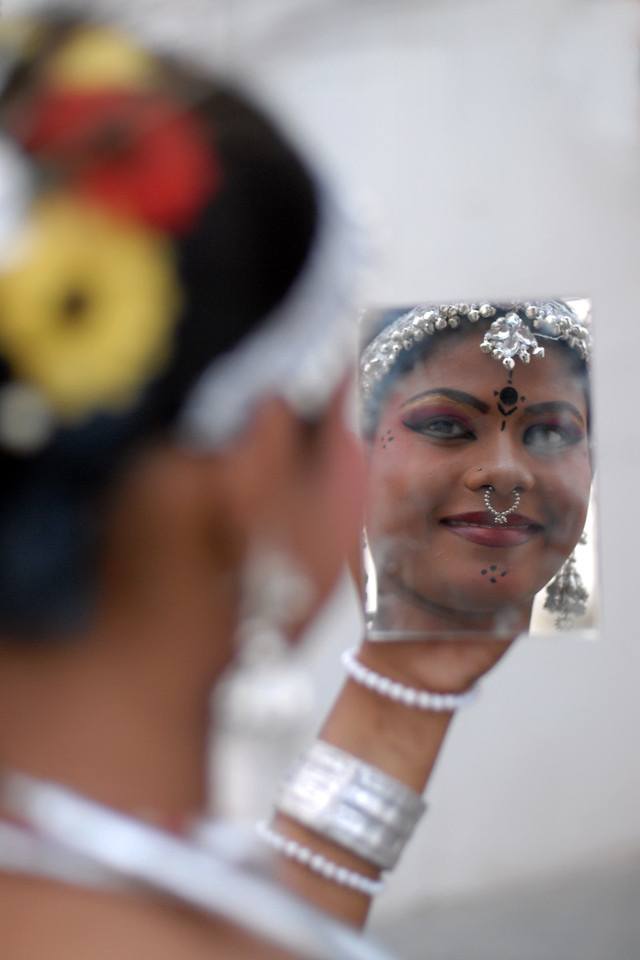 Reflection. Ladies who were part of the troupe from Orissa getting ready before their performance of song and dance at the Rajasthan Day Celebrations in Jaipur, March/April 2007, India. This young lady was using a mirror to put on her make-up.<br /> <br /> With the aim of showcasing Rajasthan State's culture & heritage and reviving the traditional sports, cuisines and folk-art, Rajasthan Diwas Celebrations were held from 21st March to 30th March 2007. Craft-Bazaar, Food Festival, Night Bazaar, Sports competitions, spectacular fire-works, Mega Cultural Concerts, and competitions for school students were organized.