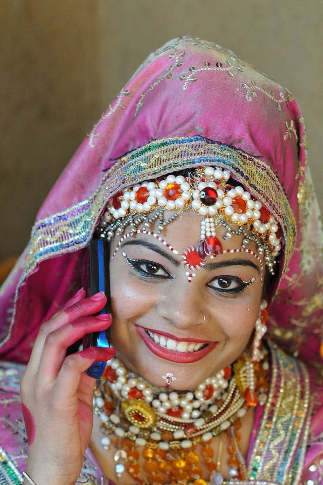 Artist who performs in Krishna Leela (Lord Krishna and Radha's dance) and plays Radha backstage on her cellphone.<br /> <br /> Surajkund Crafts Mela 2011 held near Delhi in Faridabad, Haryana, North India. The annual Suraj Kund Mela (fair) is an event held in February each year where artisans, craftsmen, musicians & dancers come together and entral thousands of visitors. It is also a great shopping bonanza and delight to the palate with the range of food.