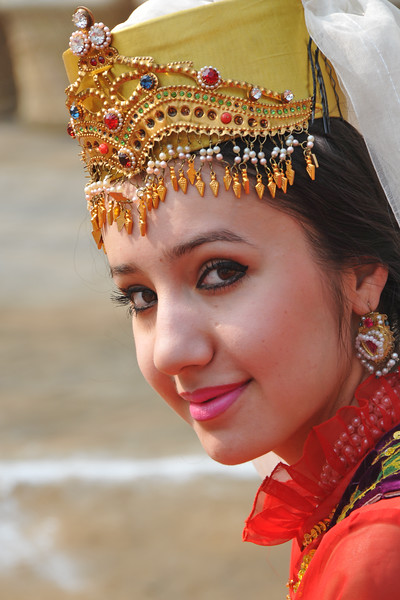 Pretty young girl artist from Uzbekistan in her traditional attire at the Surajkund Crafts Mela.<br /> <br /> Surajkund Crafts Mela 2011 held near Delhi in Faridabad, Haryana, North India. The annual Suraj Kund Mela (fair) is an event held in February each year where artisans, craftsmen, musicians & dancers come together and entral thousands of visitors. It is also a great shopping bonanza and delight to the palate with the range of food.