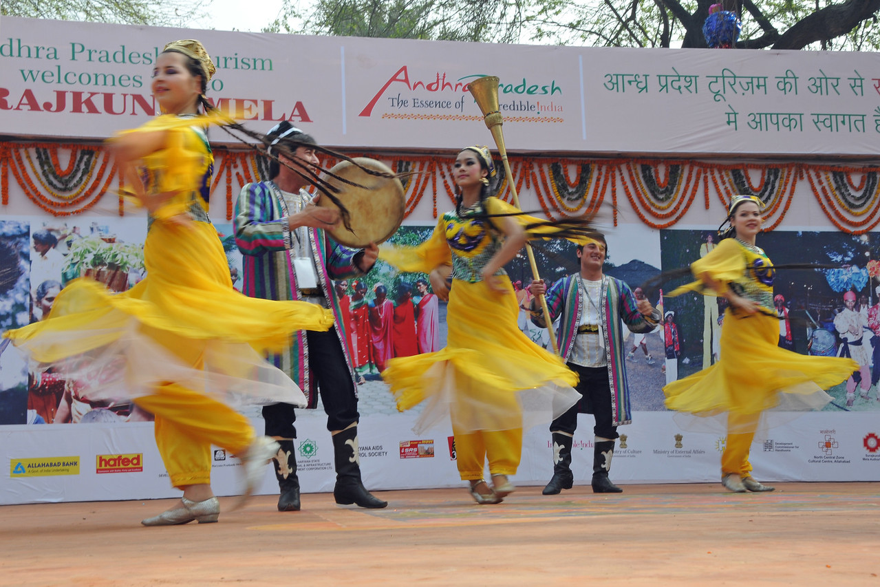 Artists from Tajikistan in colourful ethnic costumes perform on the stage at the Surajkund Crafts Mela.<br /> <br /> Surajkund Crafts Mela 2011 held near Delhi in Faridabad, Haryana, North India. The annual Suraj Kund Mela (fair) is an event held in February each year where artisans, craftsmen, musicians & dancers come together and entral thousands of visitors. It is also a great shopping bonanza and delight to the palate with the range of food.
