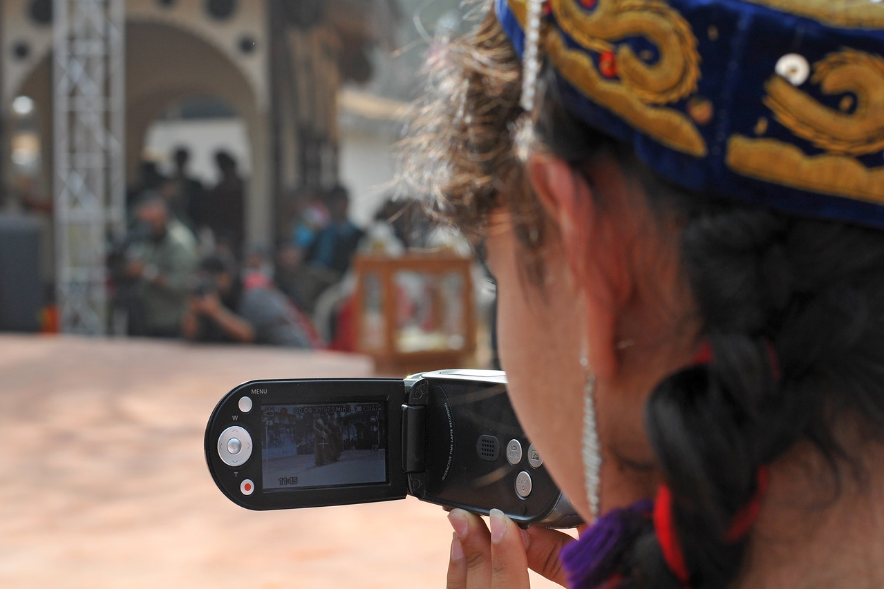 The artist from Kazakhstan at Suraj Kund taking a video and pictures of the performances.<br /> <br /> Surajkund Crafts Mela 2011 held near Delhi in Faridabad, Haryana, North India. The annual Suraj Kund Mela (fair) is an event held in February each year where artisans, craftsmen, musicians & dancers come together and entral thousands of visitors. It is also a great shopping bonanza and delight to the palate with the range of food.