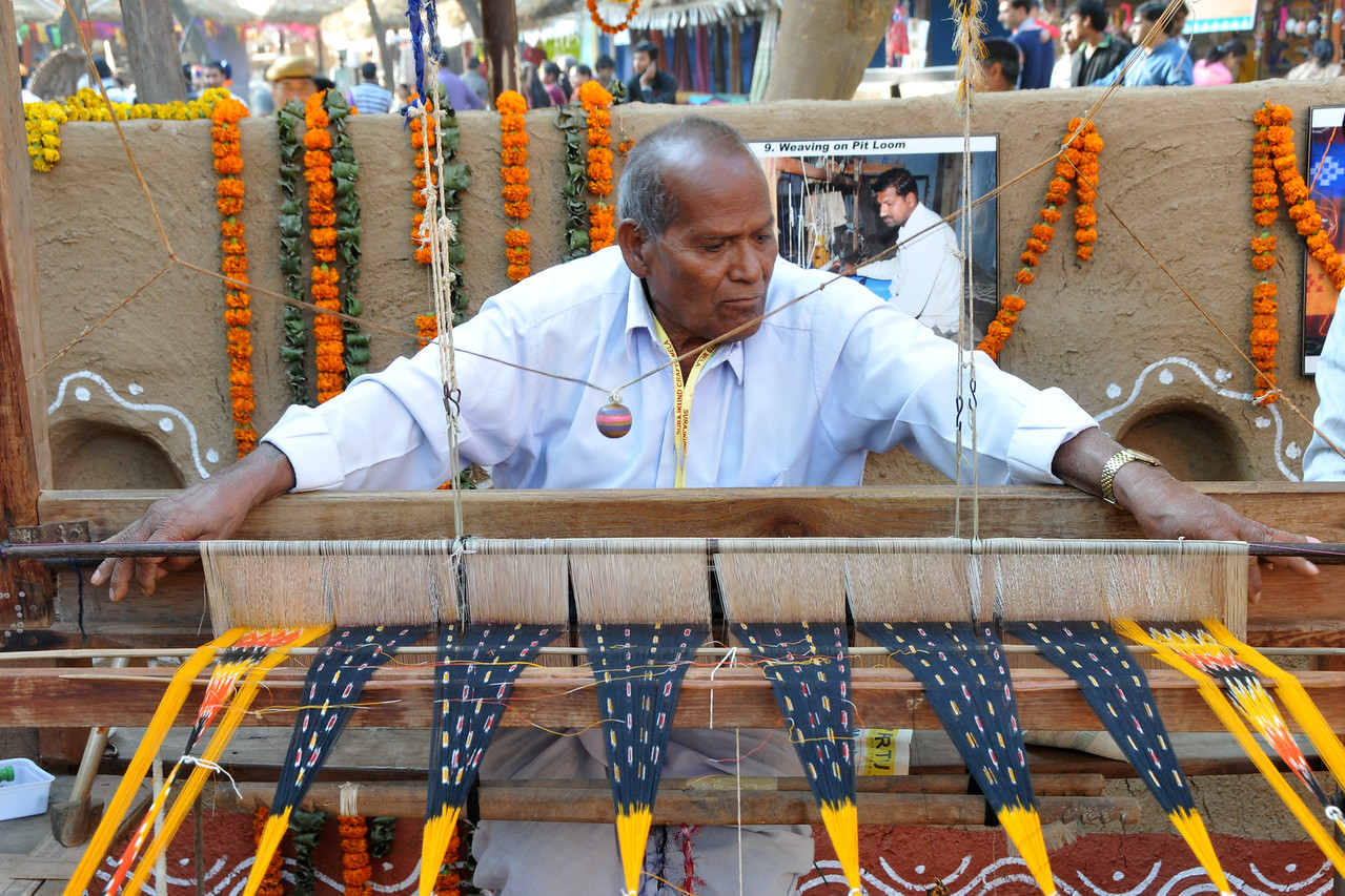 Weaving on pit loom.<br /> <br /> Surajkund Crafts Mela 2011 held near Delhi in Faridabad, Haryana, North India. The annual Suraj Kund Mela (fair) is an event held in February each year where artisans, craftsmen, musicians & dancers come together and entral thousands of visitors. It is also a great shopping bonanza and delight to the palate with the range of food.