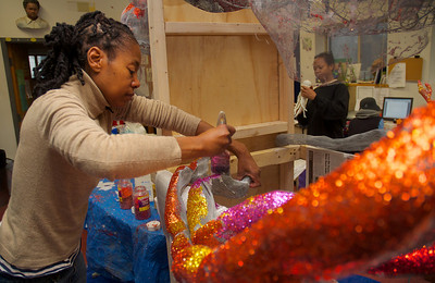 "123012, Roxbury, MA - Linda Palmer paints glitter and glue onto ""Louie the Lobster"" being built at the Hawthorne Youth and Community Center for the First Night Celebration. Herald photo by Ryan Hutton"
