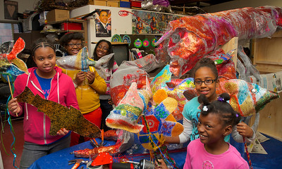 "123012, Roxbury, MA - From left, Eleanor Southerland, 12, Rayauna Moss Cousin, 14, Cincere Carkeor, 13, Sophia Gaines, 10 and Rayven Moss, 6, show off the aquatic creatures they built in front of the larger ""Louie the Lobster"" being built at the Hawthorne Youth and Community Center for the First Night Celebration. Herald photo by Ryan Hutton"