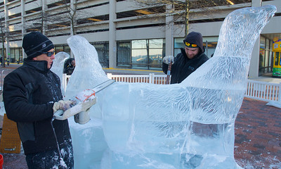 122912, Boston, MA - Don Chapelle, left, and LArs-Erik- Miller, right, of Brilliant Ice Sculptures, work on an ice sculpture outside the New England Aquarium. This year, the annual New Year's ice sculpture is of the aquarium's new fur seal pup Flaherty, his mother Ursula and his father Isaac. Herald photo by Ryan Hutton