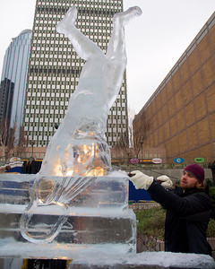 123012, Boston, MA - Lars-Erik Miller from Brilliant Ice Sculptures, works on an ice sculpture outside the Prudential Center for the First Night Celebration. Herald photo by Ryan Hutton
