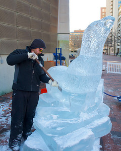 122912, Boston, MA - Lars-Erik Miller works on an ice sculpture outside the New England Aquarium. This year, the annual New Year's ice sculpture is of the aquarium's new fur seal pup Flaherty, his mother Ursula and his father Isaac. Herald photo by Ryan Hutton