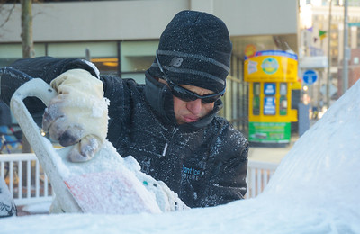 122912, Boston, MA - Don Chapelle, of Brilliant Ice Sculptures, works on an ice sculpture outside the New England Aquarium. This year, the annual New Year's ice sculpture is of the aquarium's new fur seal pup Flaherty, his mother Ursula and his father Isaac. Herald photo by Ryan Hutton