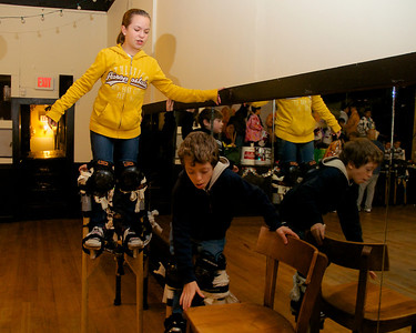 122712, Jamaica Plain, MA - Sophie Gemeinhardt, 12, gives some pointers to her younger brother Max, 9,  while practicing on stilts at Spontaneous Celebrations as practice for the First Night celebration in Boston. Herald photo by Ryan Hutton