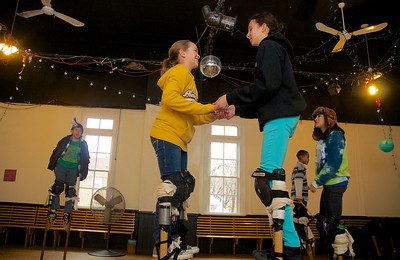 122712, Jamaica Plain, MA - Sophie Gemeinhardt, 12, left, and Mia Sheets, 12, right, use each other for balance while practicing on stilts at Spontaneous Celebrations as practice for the First Night celebration in Boston. Herald photo by Ryan Hutton