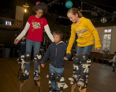 122712, Jamaica Plain, MA - Sophie Gemeinhardt, 12, right, and Serah Holley, 12, right, help Sophie's little brother Max, 9,  while practicing on stilts at Spontaneous Celebrations as practice for the First Night celebration in Boston. Herald photo by Ryan Hutton