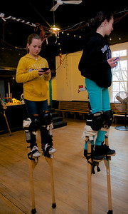 122712, Jamaica Plain, MA - Sophie Gemeinhardt, 12, left, and Mia Sheets, 12, right, pause to send a quick text while practicing on stilts at Spontaneous Celebrations as practice for the First Night celebration in Boston. Herald photo by Ryan Hutton
