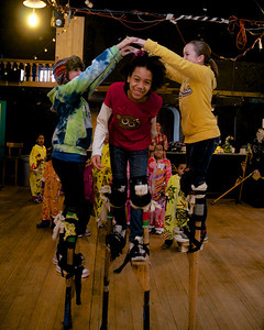 122712, Jamaica Plain, MA -  Serah Holley, 12, center, ducks under the arms of Irene Colin-Nava, 12, left, and Sophie Gemeinhardt, 12, right while practicing on stilts at Spontaneous Celebrations as practice for the First Night celebration in Boston. Herald photo by Ryan Hutton