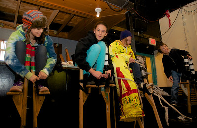 122712, Jamaica Plain, MA - From left, Irene Colin-Nava, 12, Mia Sheets, 12, Sophie Gemeinhardt, 12, and Max Gemeinhardt, 10, all tie on their stilts at Spontaneous Celebrations as practice for the First Night celebration in Boston. Herald photo by Ryan Hutton