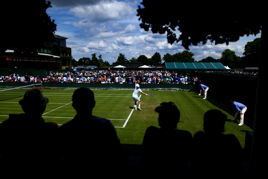 Spectators watch on as Kevin Anderson of South Africa serves during his first round match against Denis Istomin of Uzbekistan during day one of the Wimbledon Lawn Tennis Championships at the All England Lawn Tennis and Croquet Club on June 26, 2016 in London, England.
