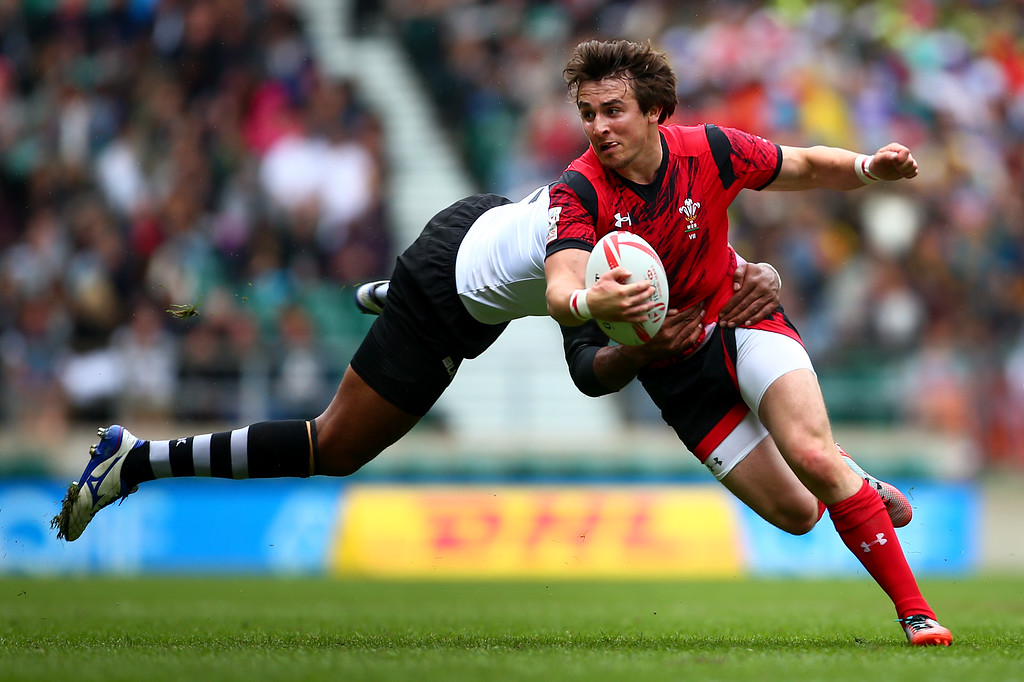 Luke Morgan of Wales is tackled by Jasa Veremalua of Figi during the pool match between Wales and Figi on day one of the HSBC London Sevens at Twickenham Stadium on May 21, 2016 in London, United Kingdom.