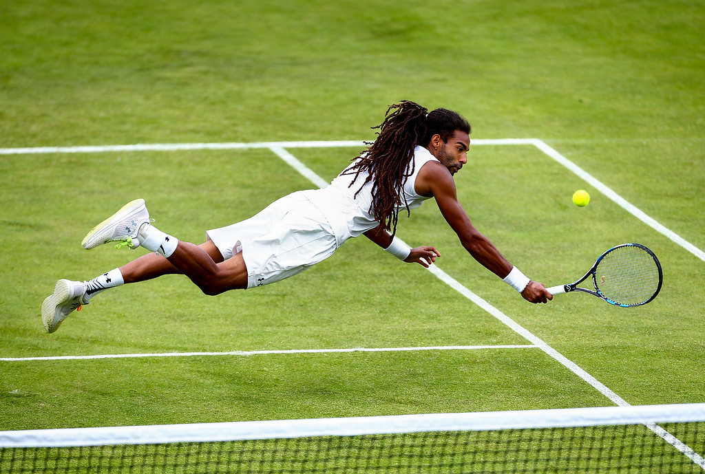 Dustin Brown of Germany dives for a backhand during his first round match against Eduardo Struvay of Colombia during day four of the Aegon Surbiton Trophy at Surbiton Racket & Fitness Club on June 7, 2016 in Surbiton, England.