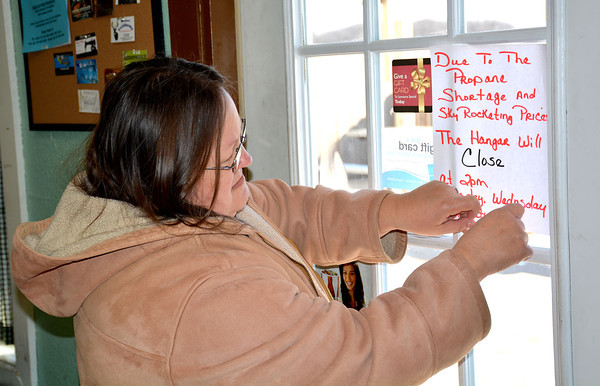 Brenda Byers, owner of The Hangar Restaurant at Percival Springs Airport, puts up a sign with her new business hours. Byers is having to cut back on hours at her restaurant due to a shortage in propane.