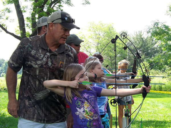 Kevin Gouchenourer helps Kelcey Stone, 6, of Effingham, fire an arrow at a range at the Ballard Nature Center at the JAKES event. Fishing, hiking and other events were also held at the nature center.