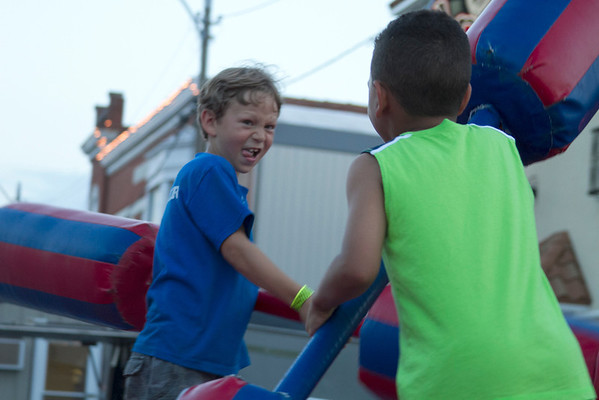 Seven-year-old Luke Weber, left, and Jaetis Schaffer, 6, play at one of the many inflatable bouncers that were available for children at the Newton Strawberry Festival. The festival spanned throughout the weekend, offering items such as homemade ice cream and a strawberry-themed basket.